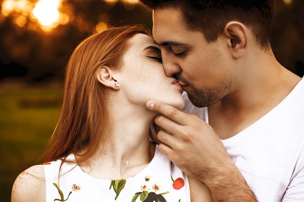 Side view portrait of a amazing young couple kissing against sunset with closed eyes while man is touching his girlfriend's face.