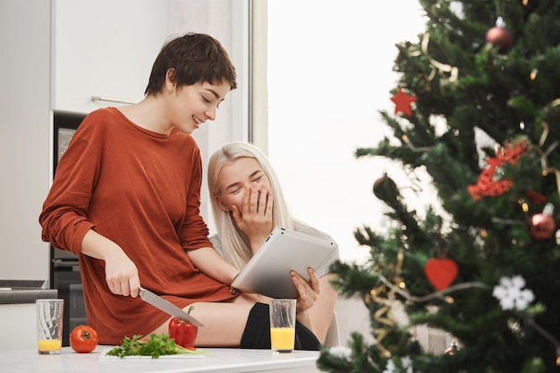 Side-view portrait of attractive skinny shirt-haired girl cutting vegetables and showing something in tablet to het friend who laughs out loud and enjoyes spending time with her