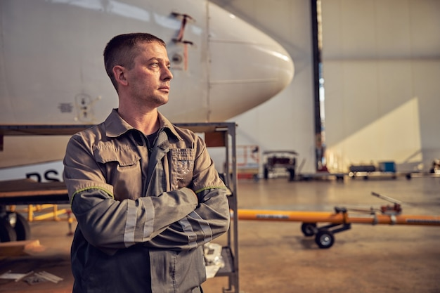 Side view portrait of aviation mechanic keeping arms crossed while standing in front of cockpit of passenger aircraft in the indoors