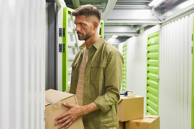 Side view portrait of bearded adult man loading cardboard boxes into self storage unit, copy space