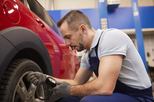 Side view portrait of bearded car mechanic checking pressure in tires during vehicle inspection in garage shop, copy space