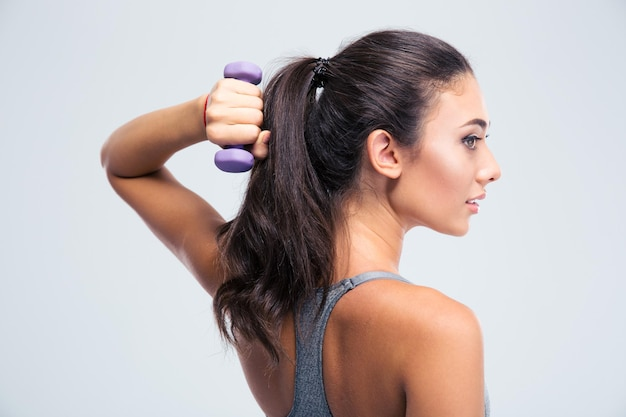 Side view portrait of a beautiful sports woman working out with dumbbells isolated on a white wall