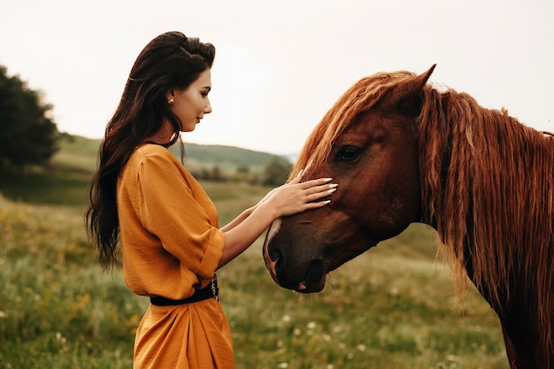 Side view portrait of a beautiful young woman with dark long hair touching gently a brown horse on a field while traveling.