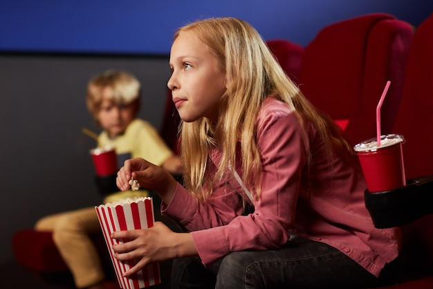 Side view portrait of blonde teenage girl watching movie in cinema theater and eating popcorn, copy space