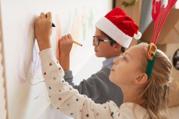 Side view portrait of boy and girl drawing on walls while wearing santa hats and antlers for christmas, copy space
