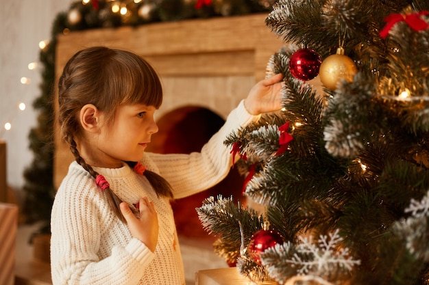 Ritratto di vista laterale della bambina affascinante con le trecce che decora l'albero di natale da solo, indossando un maglione bianco, in piedi nel soggiorno vicino al camino.