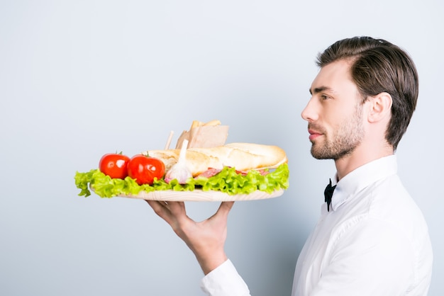 Side view portrait of confident young waiter carrying an order