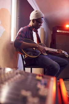 Side view portrait of contemporary african-american man playing guitar sitting on high chair