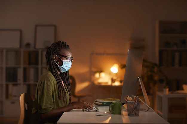 Side view portrait of contemporary african-american woman wearing mask while working in office late at night lit by computer screen, copy space