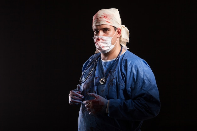 Side view portrait of crazy doctor with blood on his coat looking at the camera. man looking like a doctor for halloween.