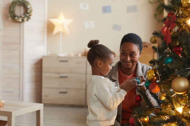 Side view portrait of cute african-american girl decorating christmas tree with smiling happy mom in cozy home interior, copy space