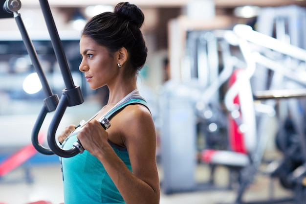 Side view portrait of cute woman workout on exercises machine in fitness gym