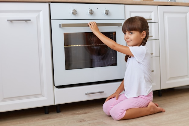 Side view portrait of dark haired female child with pigtails sitting on the floor near kitchen set, looking away, waiting for delicious pastry, wearing casual style clothing.