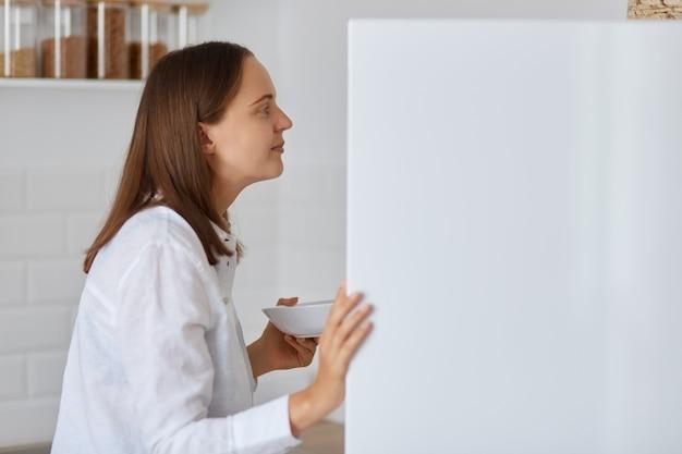Vista laterale ritratto di donna dai capelli scuri che cerca qualcosa nel frigo a casa, in piedi con il piatto in mano, indossa una camicia bianca, si sente affamato, trova cibo.