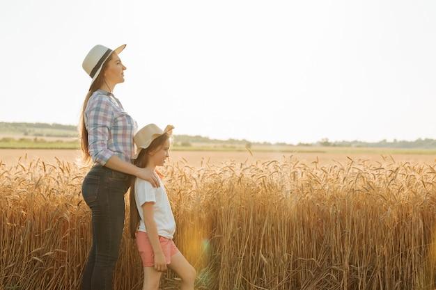 Вид сбоку портрет семьи фермеров мать с дочерью в шляпах в пшеничном золотом поле агро прогулки в ...