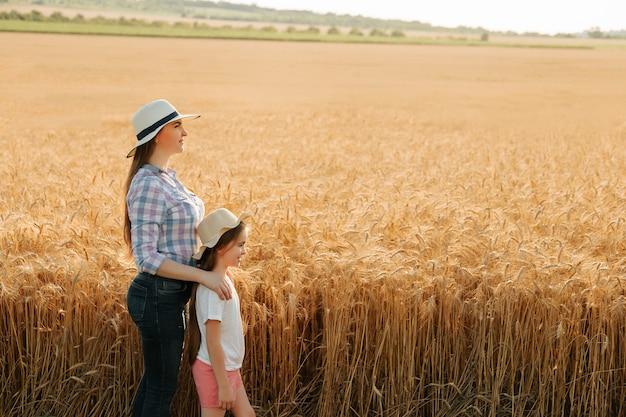 밀 황금 필드 농업 산책에 모자에 딸과 함께 농부 어머니의 측면 보기 초상화 가족...