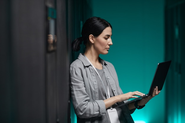 Side view portrait of female data engineer holding laptop while working with supercomputer in server room, copy space