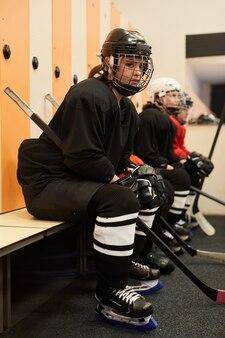 Side view portrait of female hockey team sitting in row