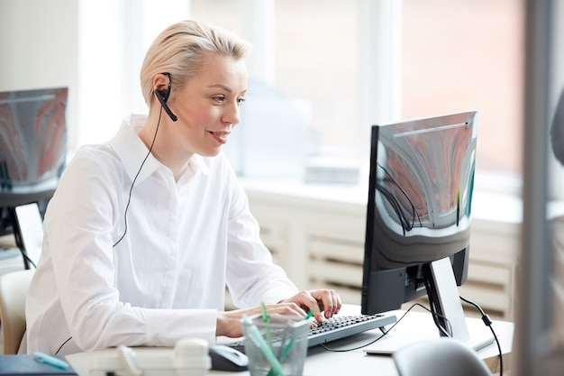 Side view portrait of female hotline operator using laptop and wearing headset while performing customer support service