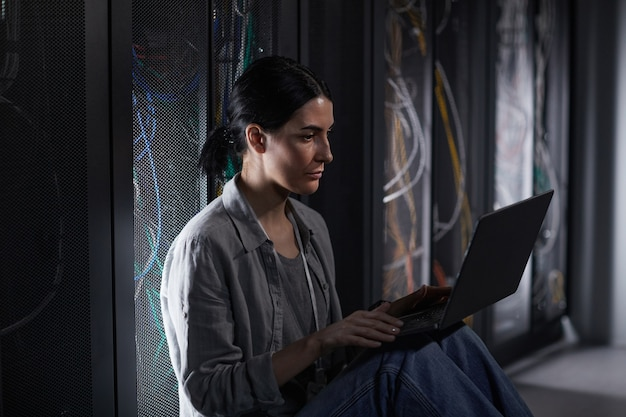 Side view portrait of female it engineer using laptop in server room while working with supercomputer at data center, copy space
