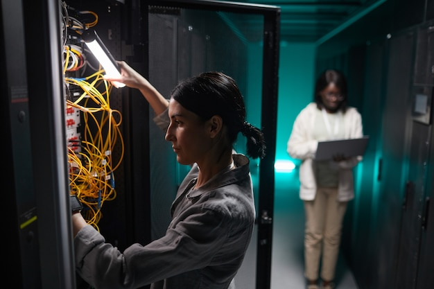 Side view portrait of female network engineer connecting cables in server cabinet while working with supercomputer in data center, copy space