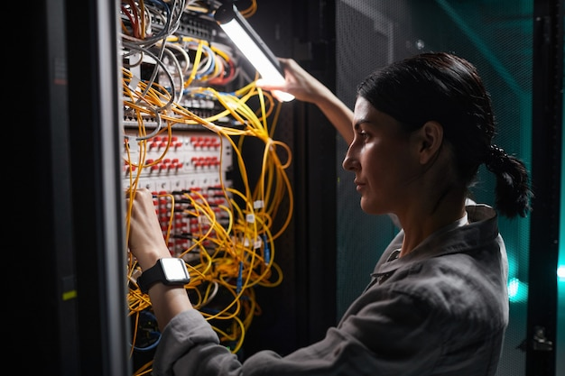 Side view portrait of female network engineer connecting cables in server cabinet while working with supercomputer in data center
