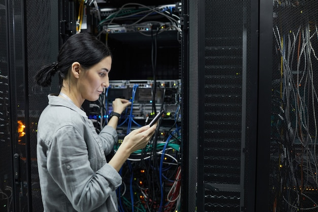 Side view portrait of female network technician connecting cables in server cabinet while setting up supercomputer at data center, copy space