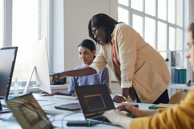 Side view portrait of female team leader instructing colleague and pointing at screen while working with multi-ethnic team of software developers in office, copy space