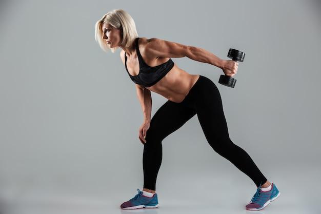 Ritratto di vista laterale di una sportiva adulta muscolare focalizzata