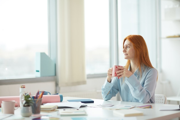 Side view portrait of freckled young woman daydreaming in modern office while drinking coffee at workplace, copy space