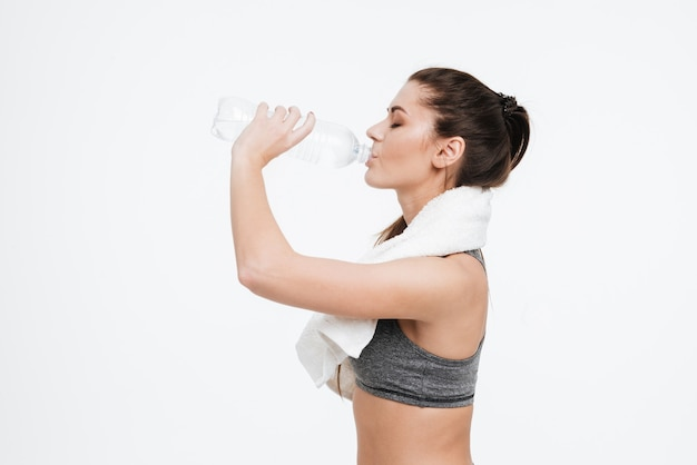 隔離された彼女の首の周りのタオルでボトルから水を飲む若いスポーツ女性の腰から上の側面図の肖像画