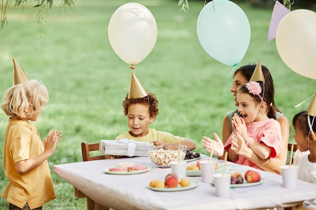 Side view portrait of group of kids enjoying outdoor birthday party in summer and giving gifts