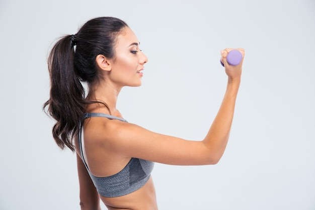 Side view portrait of a happy fitness woman working out with dumbbells isolated on a white wall