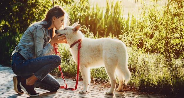 Side view portrait of a lovely young female kissing her white husky dog while walking in the park at the sunset.