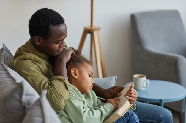 Side view portrait of loving african-american father and daughter reading while sitting on couch together in cozy home interior, copy space