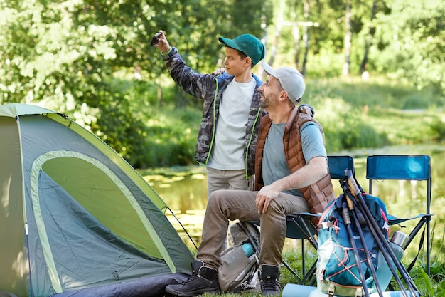 Side view portrait of loving father and son taking selfie photo while enjoying camping trip together, copy space