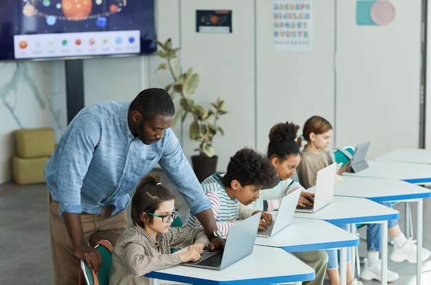 Side view portrait of male teacher helping children using computers in it class, copy space