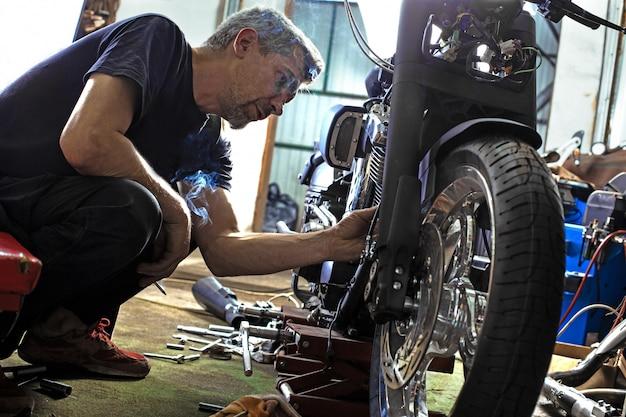 Side view portrait of man working in garage repairing motorcycle