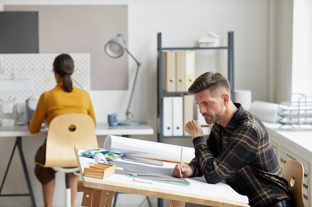 Side view portrait of mature bearded architect working on blueprints and plans while sitting at drawing desk in office,