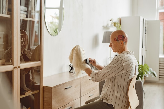 Side view portrait of modern bald woman brushing wig while sitting by mirror in home interior, alopecia and cancer awareness, copy space