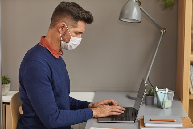 Side view portrait of modern mature man wearing mask and using laptop while working at desk in office