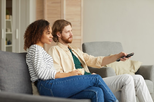 Side view portrait of modern mixed-race couple watching tv at home while relaxing on cozy sofa, focus on beaded man holding remote control