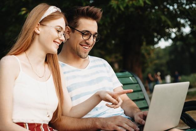 彼が外で笑顔を見ている間、彼女のボーイフレンドのラップトップの画面を指差しながら笑っている美しい若い女性の側面図の肖像画。