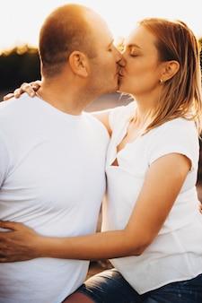 Портрет вид сбоку красивой взрослой пары, одетой в белые поцелуи против заката в обниматься лавандовом поле.