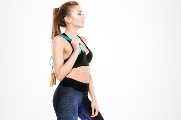 縄跳びを分離して立っているスポーツウェアの美しい女性の側面図の肖像画