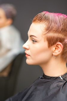 Вид сбоку портрет красивой молодой кавказской женщины с короткой розовой стрижкой, ожидающей парикмахера в салоне красоты