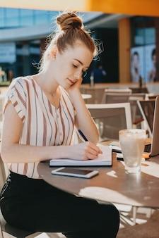 외부 커피 숍에 앉아있는 동안 노트북에 쓰는 매력적인 빨간 머리 여자의 측면보기 초상화.