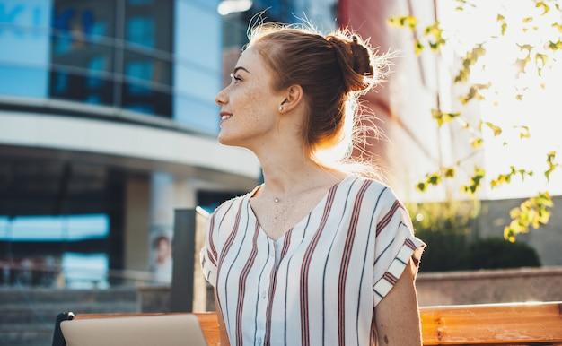노트북에서 일하는 벤치에 앉아있는 동안 멀리 웃 고 주근깨와 매력적인 젊은 빨간 머리 백인 여자의 측면보기 초상화.