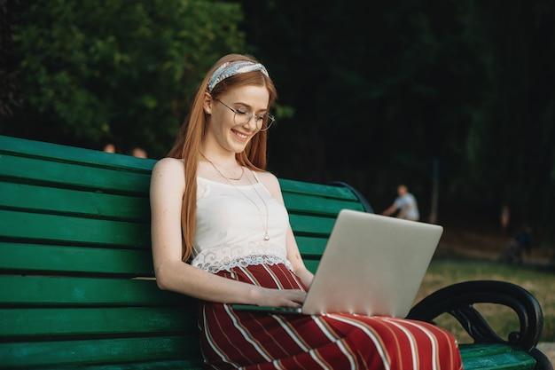 公園のベンチに座って笑っているノートパソコンの画面を見ている魅力的な若い赤毛の女性の側面図の肖像画。