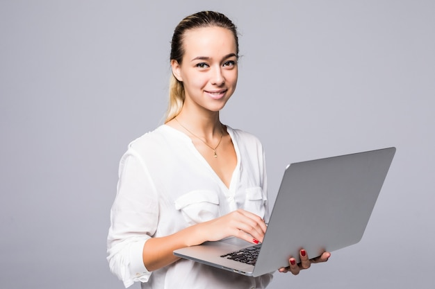Портрет жизнерадостной молодой женщины, печатающей на ноутбуке, изолированной на серой стене, вид сбоку